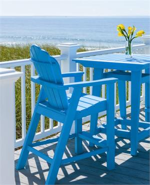 A balcony height adirondack chair is shown on pool blue on a deck overlooking the ocean. Chair is composite and is made by Seaside Casual Furniture- at GottaHaveItInc.com