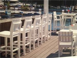 Seaside Casual MAD Bar Chair shown at a bar in white by the water.