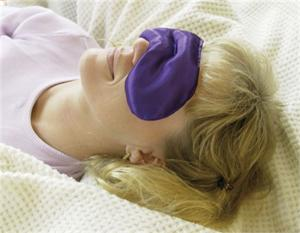 Woman lying down with an eye pack on her eyes