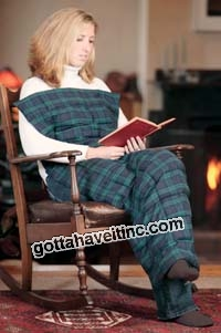 A woman in rocking chair with a blanket and a book.
