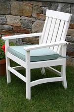 A Seaside Casual Hampton chair is shown with a stone wall in the background.