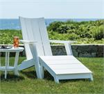 A White Contemporary Adirondack Chair with a Footstool and side table on the grass near a stone wall.