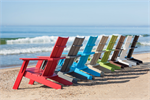 A line up of Contemporary Adirondack Chairs on a beach in 8 colors.