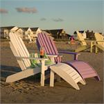 A white and a lilac shoreline adirondack chairs shown on a beach with yellow adirondacks in the background. The adirondack chairs also have ottomans in front of them.