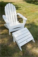 One Polywood Adirondack Chair in white shown on the grass with a polywood ottoman.